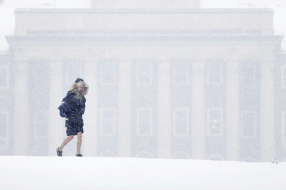 A young woman walks in view of Old Main on the Penn State University campus during a snowstorm Friday, March 20, 2015, in State College, Pa. Forecasters say a storm will dump up to 6 inches of snow on the Northeast and mid-Atlantic on Friday. New England will be on the lower end of the snow totals but even Boston, which has seen a record 108.6 inches of snow, could get an inch or more. (AP Photo/Matt Rourke)