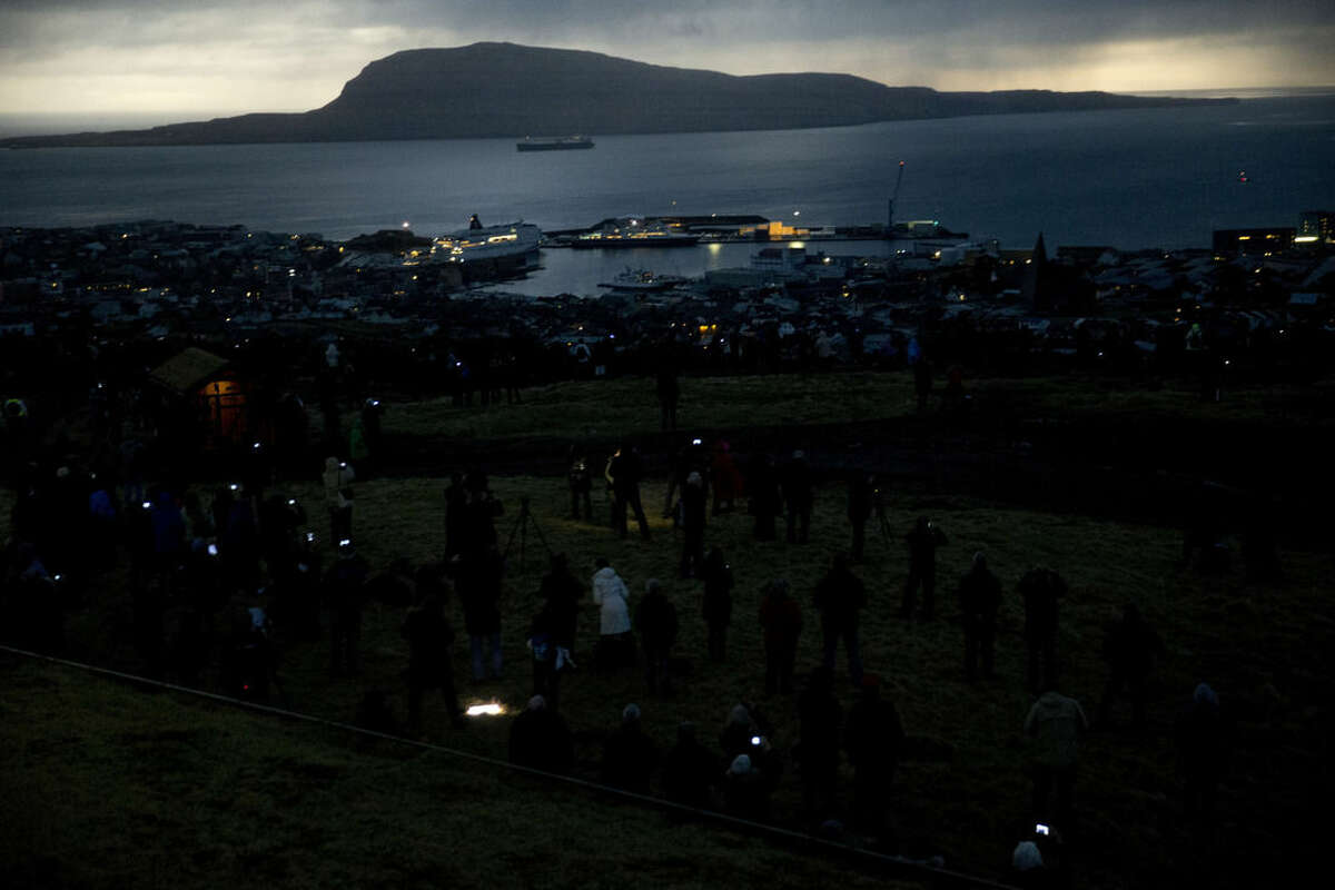 People watch in darkness during the totality of a solar eclipse on as seen from a hill beside a hotel on the edge of the city overlooking Torshavn, the capital city of the Faeroe Islands, Friday, March 20, 2015. For months, even years, accommodation on the remote Faeroe Islands has been booked out by fans who don't want to miss an almost three-minute-long astronomical sensation. Now they just have to hope the clouds will blow away so they can fully experience Friday's brief total solar eclipse. (AP Photo/Matt Dunham)