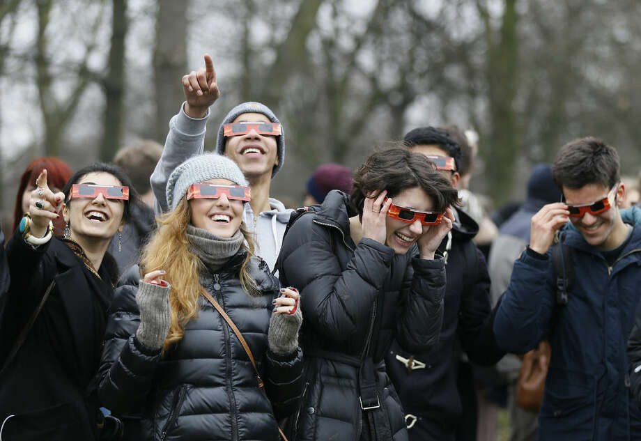 Visitors try on their solar glasses in preparation to view the eclipse in Regents Park in London, Friday, March 20, 2015. Due to heavy cloud cover, the eclipse was not visible in London. (AP Photo/Kirsty Wigglesworth)