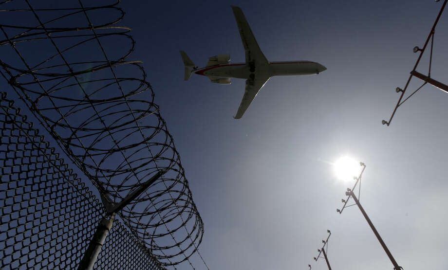 ADVANCE FOR USE MONDAY, APRIL 13, 2014 AND THEREAFTER - In this Friday, Feb. 6, 2015 photo, a passenger jet flies over the perimeter fence at the Los Angeles International Airport as it lands. Several hundred times from 2004 to 2015, intruders have hopped fences, slipped past guardhouses, crashed their cars through gates or otherwise breached perimeter barriers at more than two dozen of the busiest U.S. airports - sometimes even managing to climb aboard jets. (AP Photo/Chris Carlson)