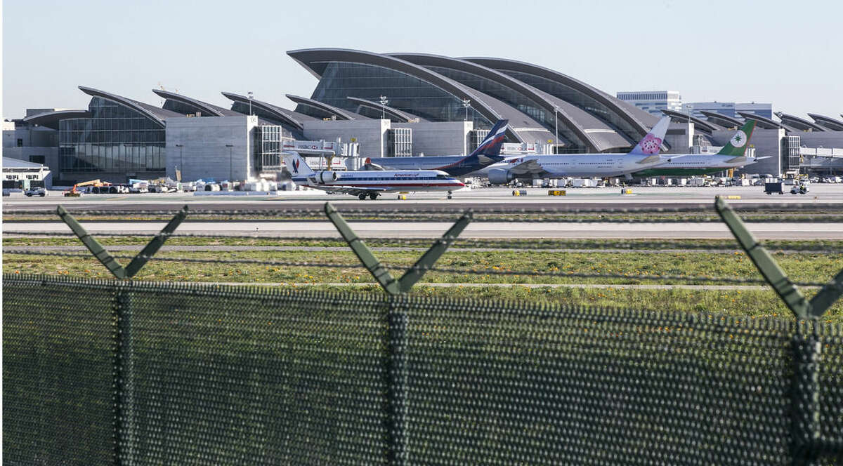 ADVANCE FOR USE MONDAY, APRIL 13, 2014 AND THEREAFTER - In this Friday, Jan. 23, 2015 photo, passenger planes sit on the tarmac behind the perimeter fence at the Los Angeles International Airport. Several hundred times from 2004 to 2015, intruders have hopped fences, slipped past guardhouses, crashed their cars through gates or otherwise breached perimeter barriers at more than two dozen of the busiest U.S. airports - sometimes even managing to climb aboard jets. (AP Photo/Damian Dovarganes)