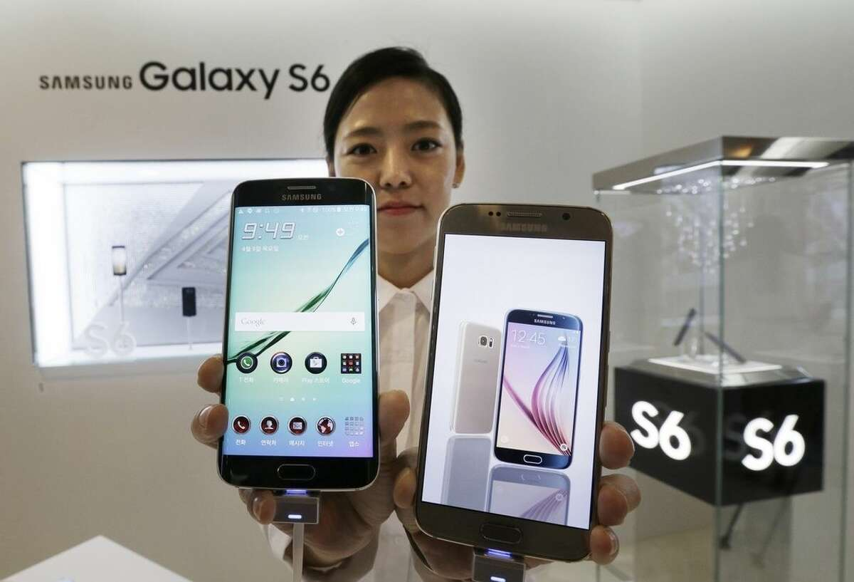 """A model poses with a Samsung Electronics Co.'s Galaxy S6, right, and Galaxy S6 Edge, left, smartphones during its launch event at company's headquarter in Seoul, South Korea, Thursday, April 9, 2015. When Samsung dubbed development of its latest smartphones """"Project Zero,"""" it was sounding a note of desperation as sales tumbled and it lost pole position in the crucial Chinese market to rivals Xiaomi and Apple .(AP Photo/Ahn Young-joon)"""