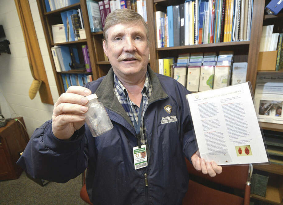 Hour Photo/Alex von Kleydorff Thomas Closter, City of Norwalk Health Department, Director of Environmental Services holds dead bedbugs in a vial and in a plastic bag that were brought in by residents for identification.