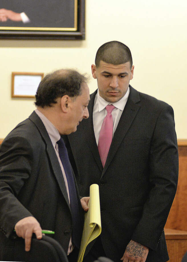 Defense attorney, James Sultan talks to former New England Patriots football player Aaron Hernandez in the court room of the Bristol County Superior Court House in Fall River, Mass., before the jury begin their deliberations, Wednesday, April 8, 2015. Hernandez is accused of the murder of Odin Lloyd in June 2013. (AP Photo/Faith Ninivaggi, Pool)