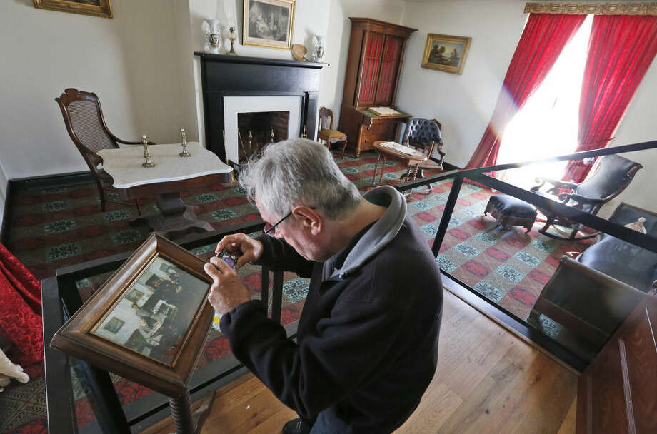 A visitor photographs a depiction of the surrender of the Confederate army in the parlor of the reconstructed McLean house at the Appomattox Court House National Historical Park in Appomattox, Va., Joshua Malatino and Amanda Scott. Confederate General Robert E. Lee surrendered his approximately 28,000 troops to Union General Ulysses S. Grant in the front parlor of Wilmer McLean's home in Appomattox Court House, Virginia, effectively ending the American Civil War. (AP Photo/Steve Helber)