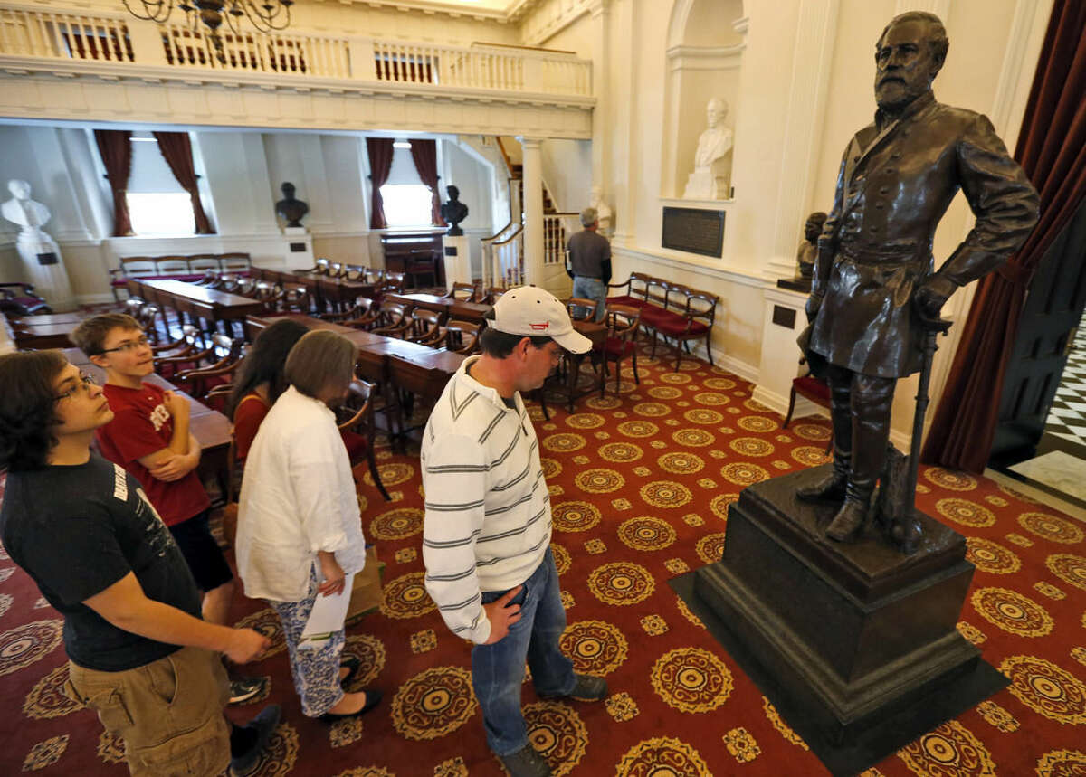 FOR RELEASE SATURDAY, APRIL 4, 2015, AT 3:00 A.M. EDT- Rob Orrison, center with cap, looks over the inscription on the statue of Confederate General Robert E. Lee, during a tour of the Old House chambers at the Capitol in Richmond, Va., Thursday, April 2, 2015. Orrison has been to 60-plus battlefields in four years during the Civil War's 150th anniversary which takes as much passion and commitment as getting married or having a child. (AP Photo/Steve Helber)