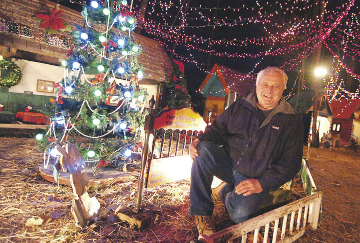 Photo/Alex von Kleydorff. Rick Setti stops off in Santas Village, part of the extreme holiday decorations he as constructed at his Norwalk home.