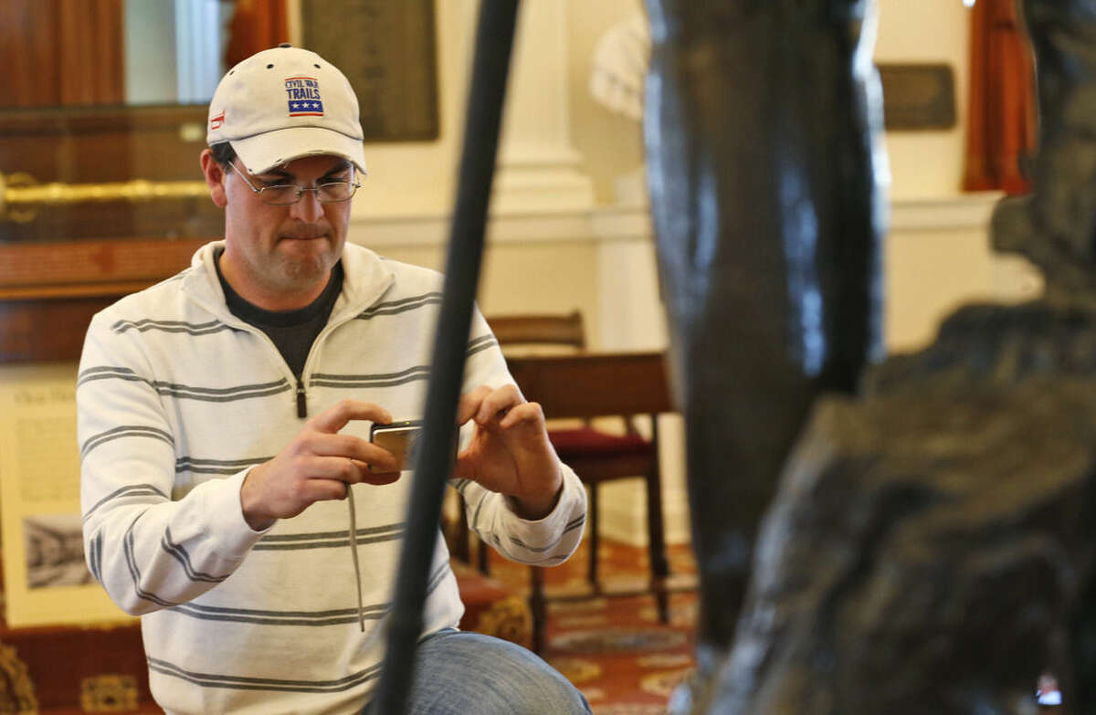 FOR RELEASE SATURDAY, APRIL 4, 2015, AT 3:00 A.M. EDT.- Rob Orrison takes a photo of the inscription on the statue of Confederate General Robert E. Lee, during a tour of the Old House chambers at the Capitol in Richmond, Va., Thursday, April 2, 2015. Orrison has been to 60-plus battlefields in four years during the Civil War's 150th anniversary which takes as much passion and commitment as getting married or having a child. (AP Photo/Steve Helber)