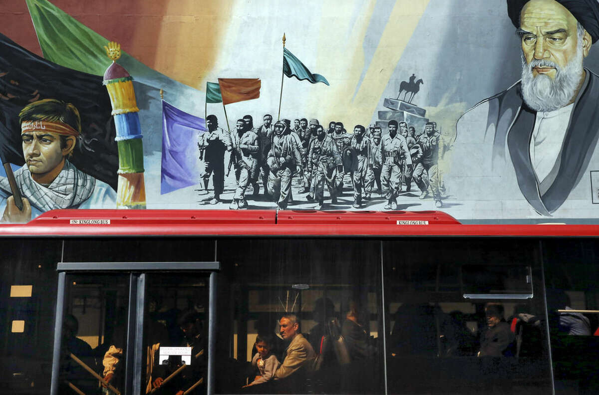 AP10ThingsToSee - Passengers travel on a public bus at the Enqelab-e-Eslami (Islamic Revolution) street under a mural depicting the late Iranian revolutionary founder Ayatollah Khomeini, right, and members of Basij paramilitary force, in Tehran, Iran, Tuesday, March 31, 2015. (AP Photo/Vahid Salemi)