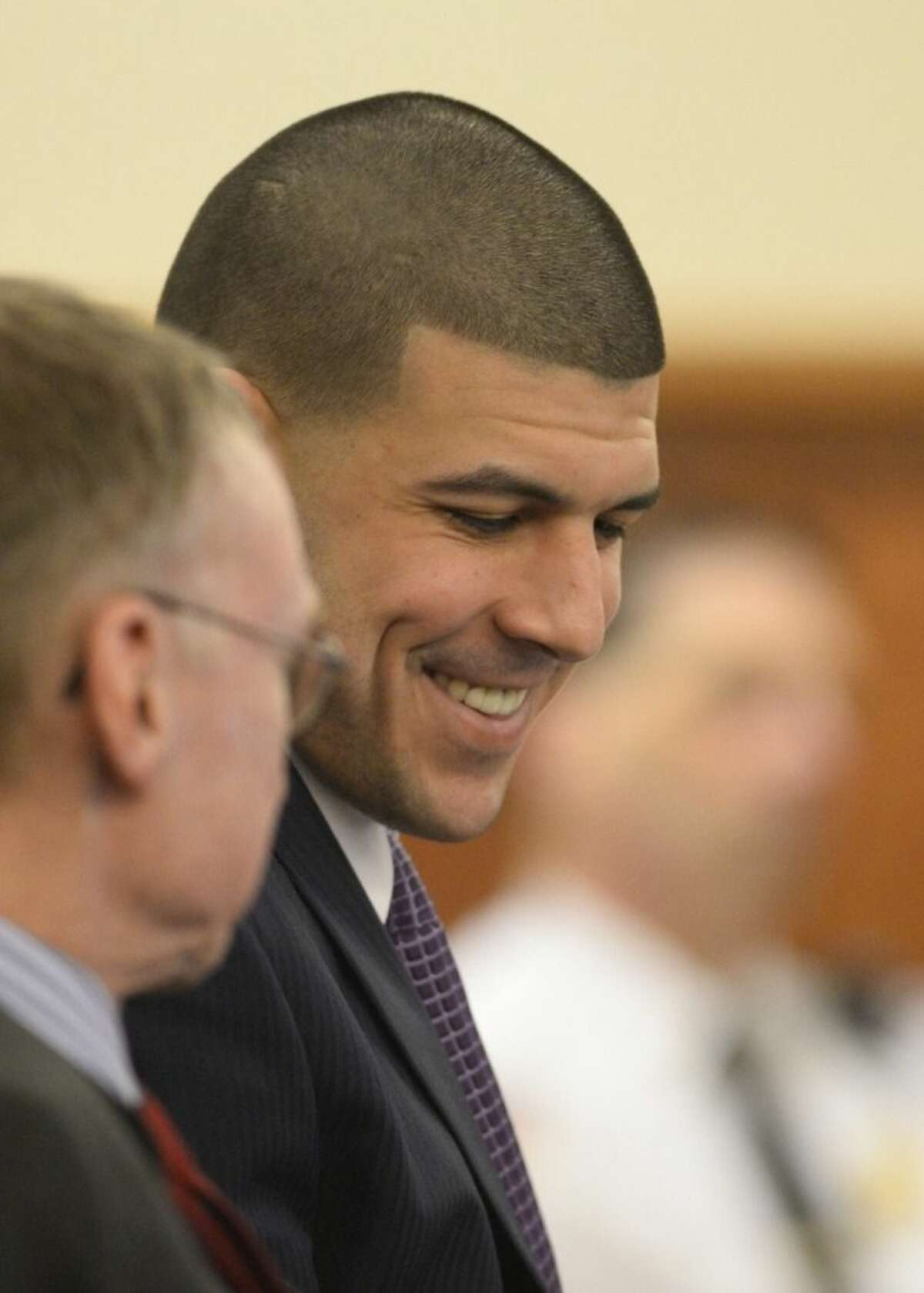 Former New England Patriots football player Aaron Hernandez smiles during his murder trial at the Bristol County Superior Court in Fall River, Mass., on Friday, April 3, 2015. Hernandez is charged with killing Odin Lloyd. (AP Photo/CJ Gunther, Pool)