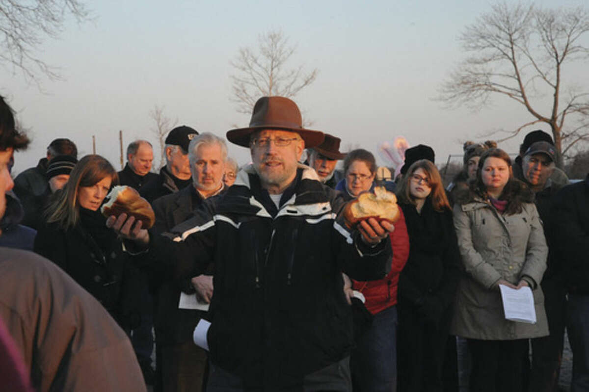 Rev. Ed Horn from United Methodist Church breaks bread at the Ecumenical Sunrise Service on Easter Sunday at Compo Beach in Westport. Hour photo/Matthew Vinci