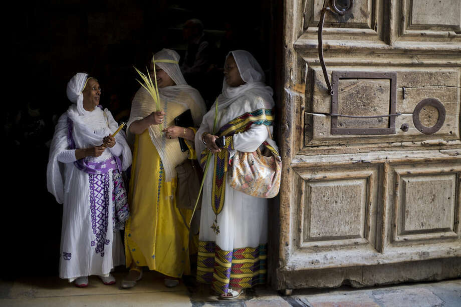 Orthodox Christian women hold palm fond's at the Church of the Holy Sepulcher, traditionally believed by many to be the site of the crucifixion and burial of Jesus Christ during Orthodox Palm Sunday, in Jerusalem, Sunday, April 5, 2015. Christians in the Holy Land and across the world are celebrating Easter, commemorating the day followers believe Jesus was resurrected in Jerusalem 2,000 years ago. (AP Photo/Ariel Schalit)