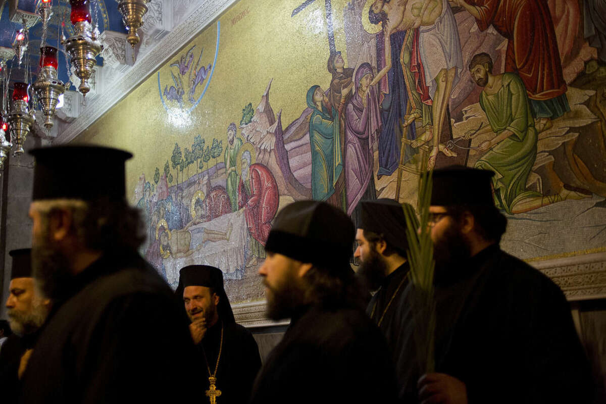Greek Orthodox priests hold palm fond in the Church of the Holy Sepulcher, traditionally believed by many to be the site of the crucifixion and burial of Jesus Christ during Orthodox Palm Sunday, in Jerusalem, Sunday, April 5, 2015. Christians in the Holy Land and across the world are celebrating Easter, commemorating the day followers believe Jesus was resurrected in Jerusalem 2,000 years ago. (AP Photo/Ariel Schalit)