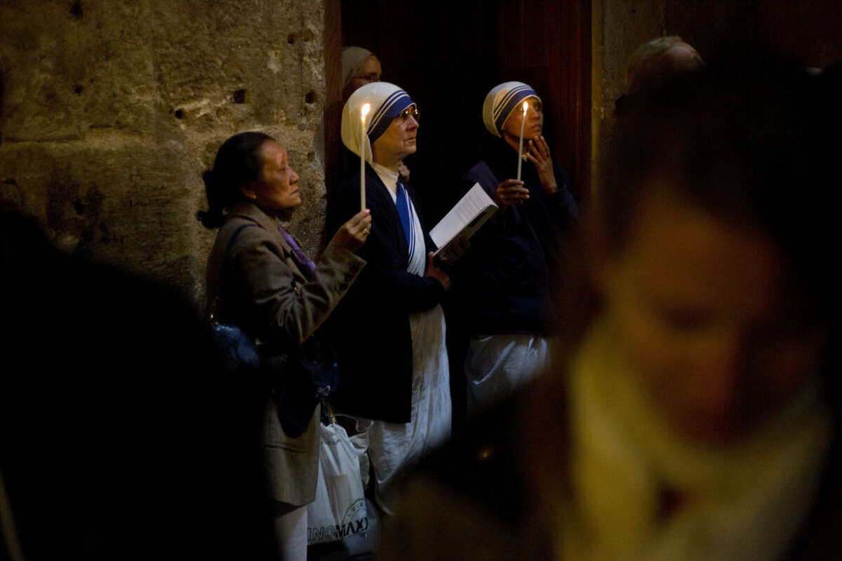 Christian women and nuns pray in the Church of the Holy Sepulcher, traditionally believed by many to be the site of the crucifixion and burial of Jesus Christ, during Orthodox Palm Sunday, in Jerusalem, Sunday, April 5, 2015. Christians in the Holy Land and across the world are celebrating Easter, commemorating the day followers believe Jesus was resurrected in Jerusalem 2,000 years ago. (AP Photo/Ariel Schalit)