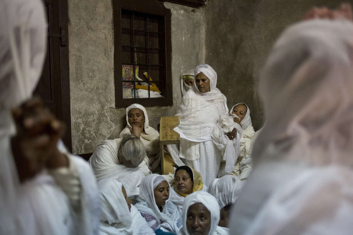 Ethiopian Orthodox Christian women pray at Deir El Sultan outside the Church of the Holy Sepulcher, traditionally believed by many to be the site of the crucifixion and burial of Jesus Christ during Orthodox Palm Sunday, in Jerusalem, Sunday, April 5, 2015. Christians in the Holy Land and across the world are celebrating Easter, commemorating the day followers believe Jesus was resurrected in Jerusalem 2,000 years ago. (AP Photo/Ariel Schalit)