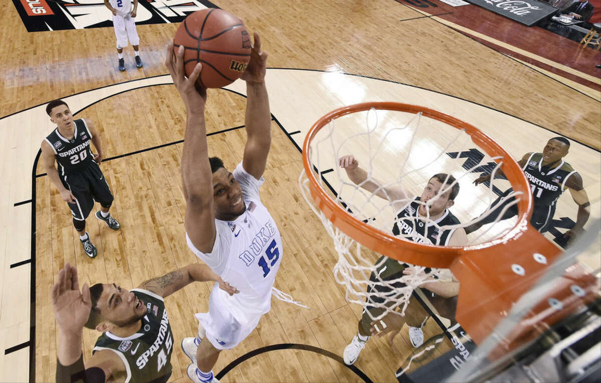 Duke's Jahlil Okafor (15) dunks the ball in front of Michigan State's Denzel Valentine (45) during the first half of the NCAA Final Four tournament college basketball semifinal game Saturday, April 4, 2015, in Indianapolis. (AP Photo/Chris Steppig, Pool)