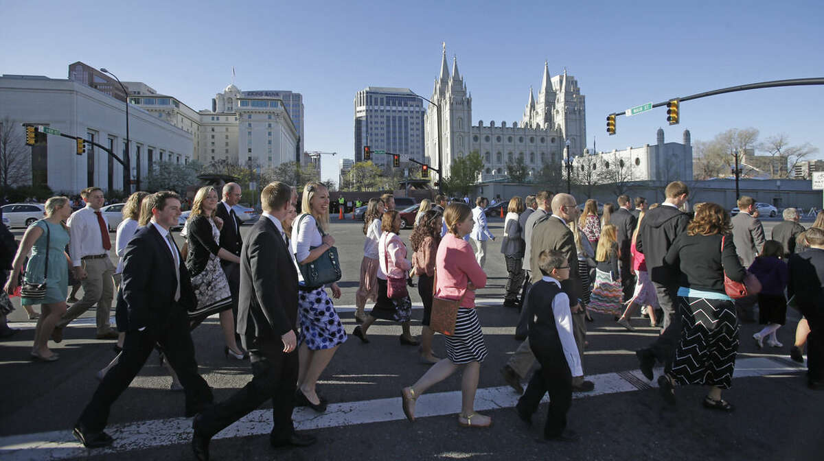 People walk past the Salt Lake Temple on the way to the opening session of the Mormon church conference Saturday, April 4, 2015, in Salt Lake City. More than 100,000 people will file in and out of the church's conference center over five sessions Saturday and Sunday. (AP Photo/Rick Bowmer)