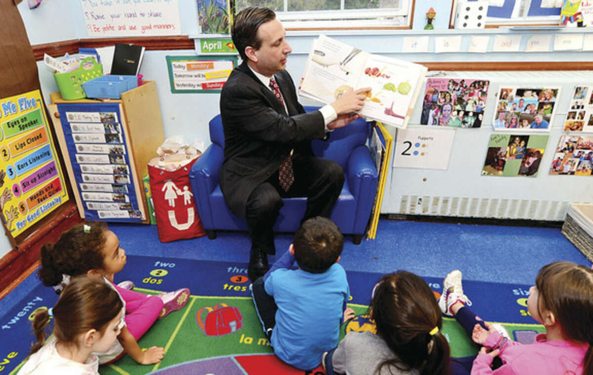 """Hour photo/Erik Trautmann In celebration of the Week of the Young Child, State Senate Majority Leader Bob Duff was a guest at Carousel Preschool, where he read """"Dragons Love Tacos"""" to 4-year-old students Tuesday."""