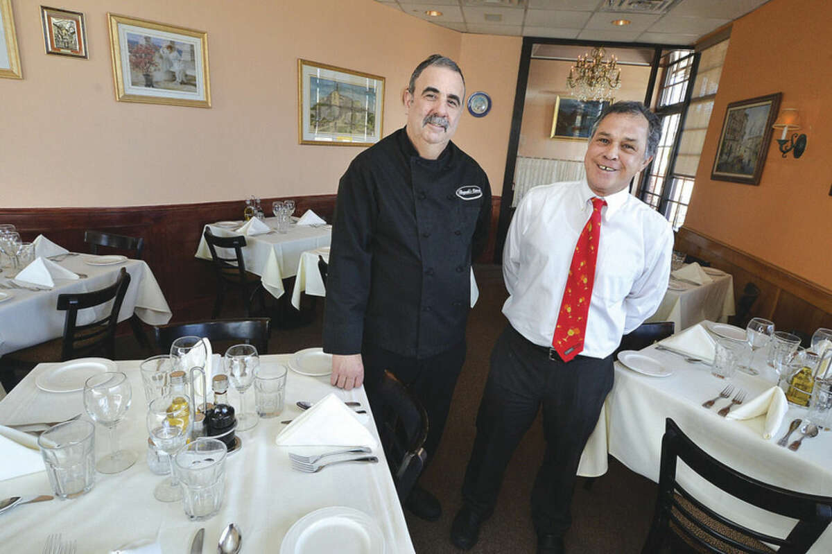 Hour photo/Alex von Kleydorff Pasquale's Osteria owner Pasquale Poccia, left, and head waiter Tony Ospina in the dining room.