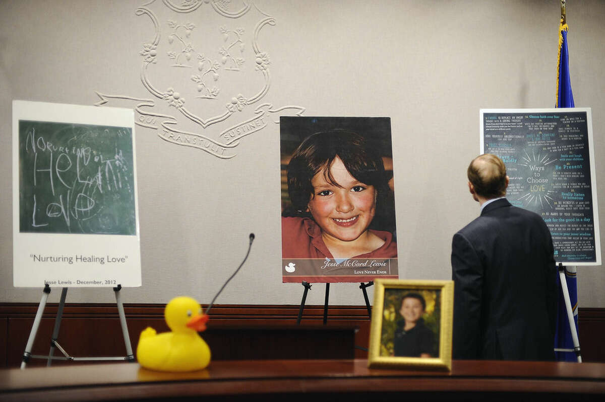 Sen. Richard Blumenthal, D-Conn., looks at a display that includes a photograph of Sandy Hook School shooting victim Jesse Lewis before a news conference at the Legislative Office Building, Monday, April 13, 2015, in Hartford, Conn. The Connecticut congressional delegation is backing federal legislation that would honor Lewis and provide expanded support to train teachers in social and emotional learning. (AP Photo/Jessica Hill)