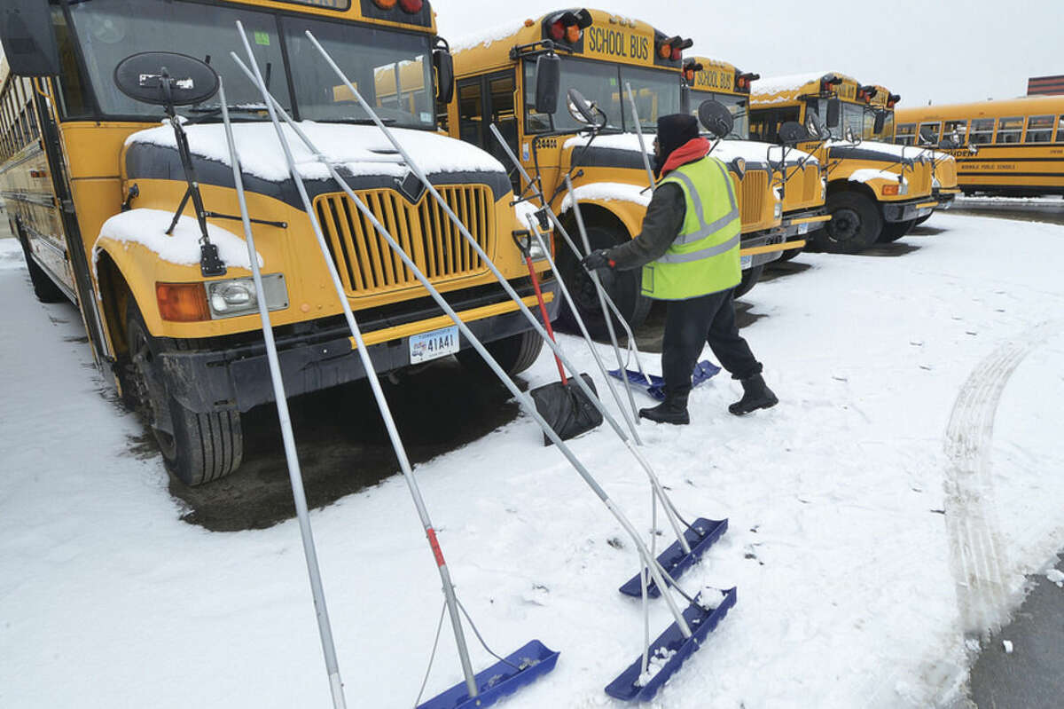 Hour file photo/Alex von Kleydorff School buses are cleared of snow at the First Student bus depot on Wilson Avenue in Norwalk.