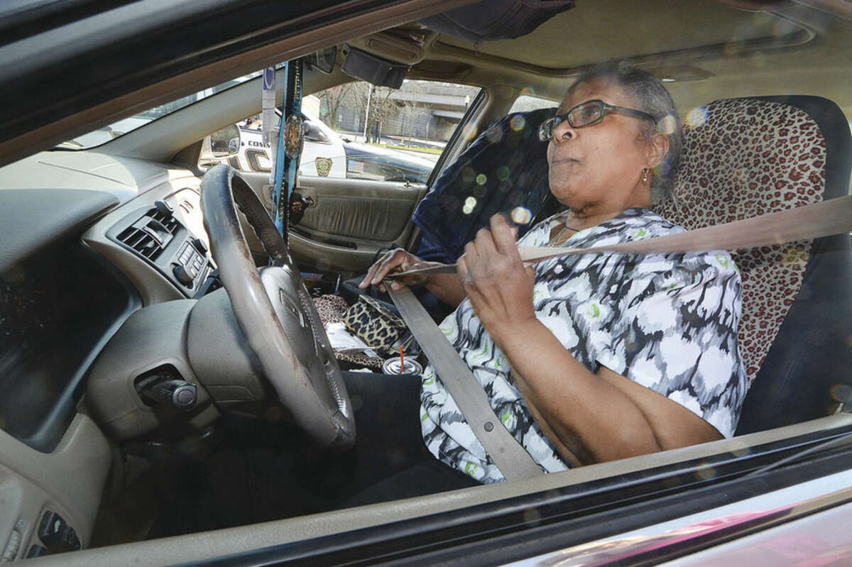 Hour Photo/Alex von Kleydorff Norwalk's Bernadette Gaskin buckles up after being issued a ticket for talking on her cell phone during distracted driving enforcement on Tuesday along West Avenue.