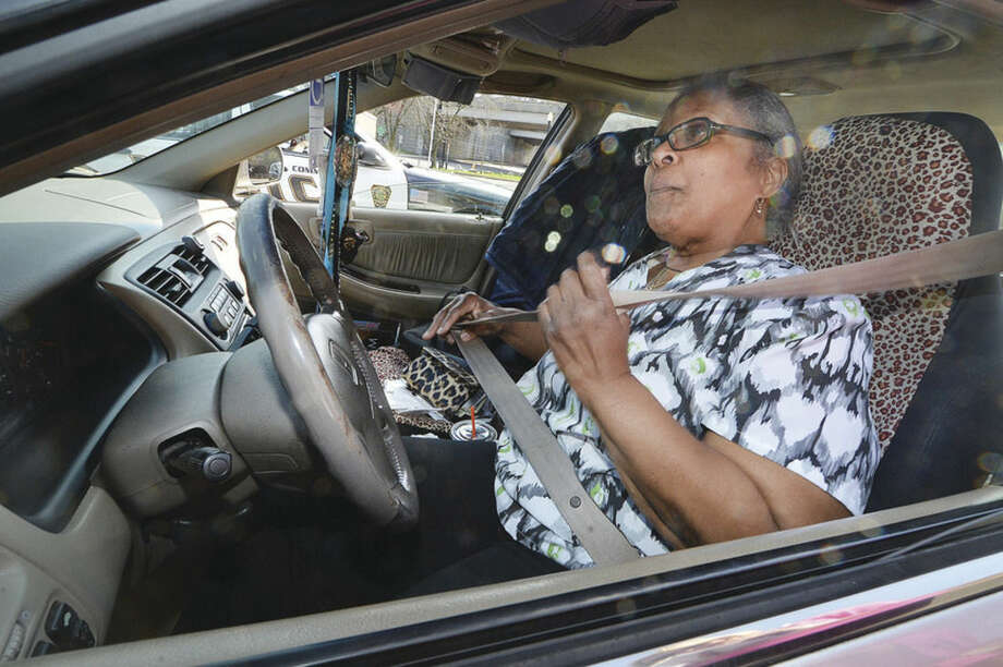 Hour Photo/Alexvon KleydorffNorwalk's Bernadette Gaskin buckles up after being issued a ticket for talking on her cell phone during distracted driving enforcement on Tuesday along West Avenue.