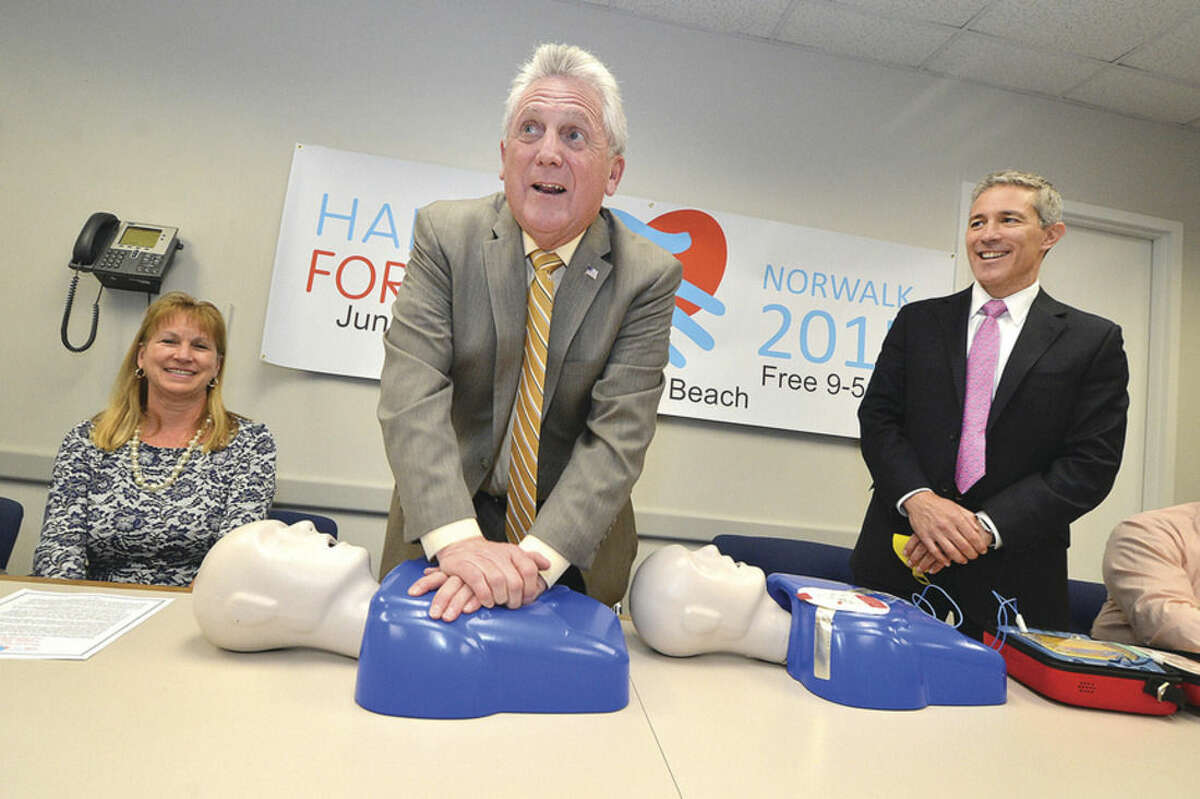 Hour photo/Alex von Kleydorff Mayor Harry Rilling practices hands-only compression during a kickoff for Hands For Life Norwalk 2015 with cardiologist Dr. Thomas Nero, right; and Ann Bartolone, RN, director of cardivascular clinical operations at Norwalk Hospital, left.