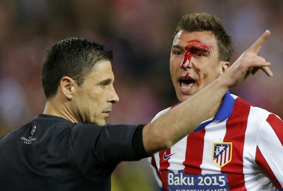 FILE - In this April 14, 2015 file photo Atletico's Mario Mandzukic, right, argues with referee Milorad Mazic, left, from Serbia after suffering an injury during the Champions League quarterfinal, first leg soccer match between Atletico de Madrid and Real Madrid at the Vicente Calderon stadium in Madrid, Spain. (AP Photo/Daniel Ochoa de Olza, file)