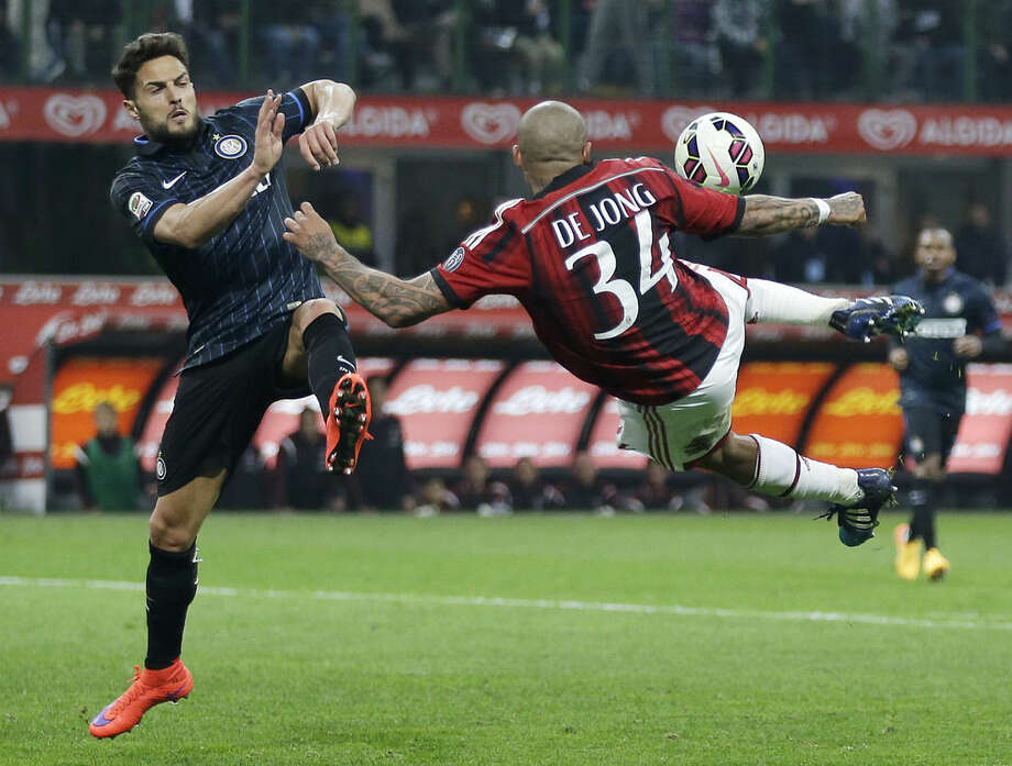 AC Milan's Nigel de Jong, right, kicks the ball as Inter Milan's Danilo D'Ambrosio tries to stop him during the Serie A soccer match between Inter Milan and AC Milan at the San Siro stadium in Milan, Italy, Sunday, April 19, 2015. (AP Photo/Antonio Calanni)