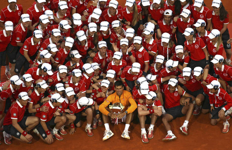 Novak Djokovic of Serbia, center, holds his cup after defeating Thomas Berdych of Czech Republic in their final match of the Monte Carlo Tennis Masters tournament, as he poses for a photograph with ball boys, in Monaco, Sunday, April 19, 2015. (AP Photo/Lionel Cironneau)