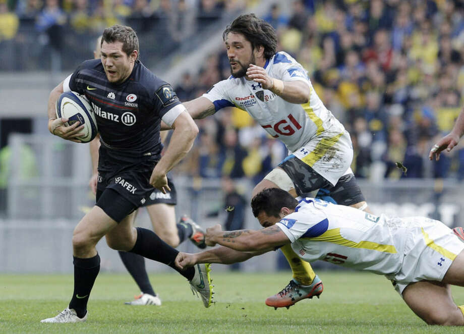 FILE - In this April 18, 2015 file photo Saracens' Alex Goode, left, is tackled by Clermont Ferrand's Julien Bardy, center, and Ludovic Radoslavjevic, right, during their Rugby European Champions Cup semifinal match in Saint-Etienne, central France. (AP Photo/Laurent Cipriani, file)