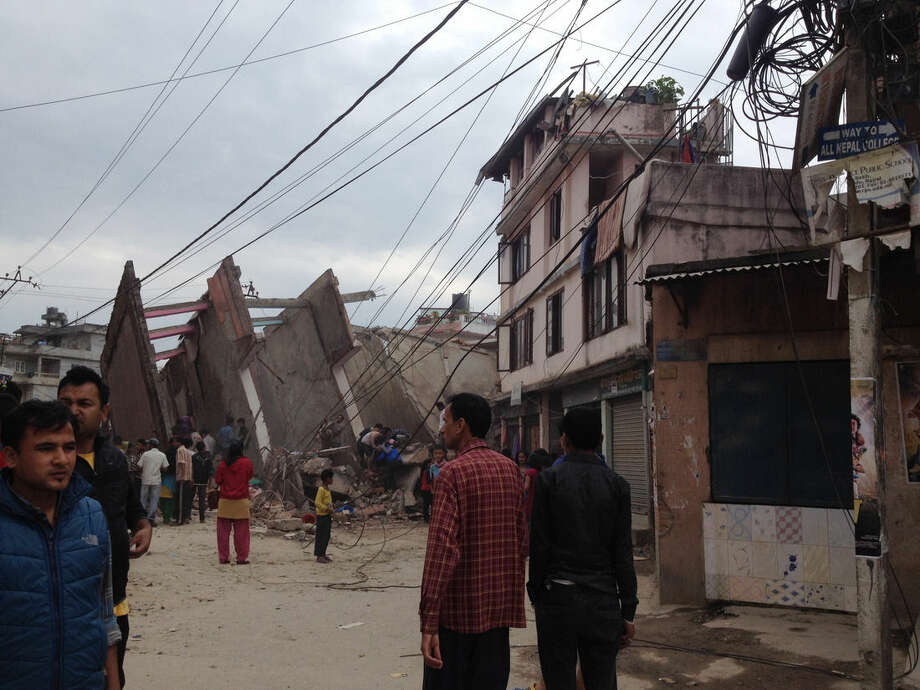 In this photo provided by Guna Raj Luitel, people walk next to ruble after an earthquake in Kathmandu, Nepal, Saturday, April 25, 2015. A powerful earthquake shook Nepal's capital and the densely populated Kathmandu Valley before noon Saturday, collapsing houses, leveling centuries-old temples and cutting open roads in the worst temblor in the Himalayan nation in over 80 years. (Guna Raj Luitel via AP)