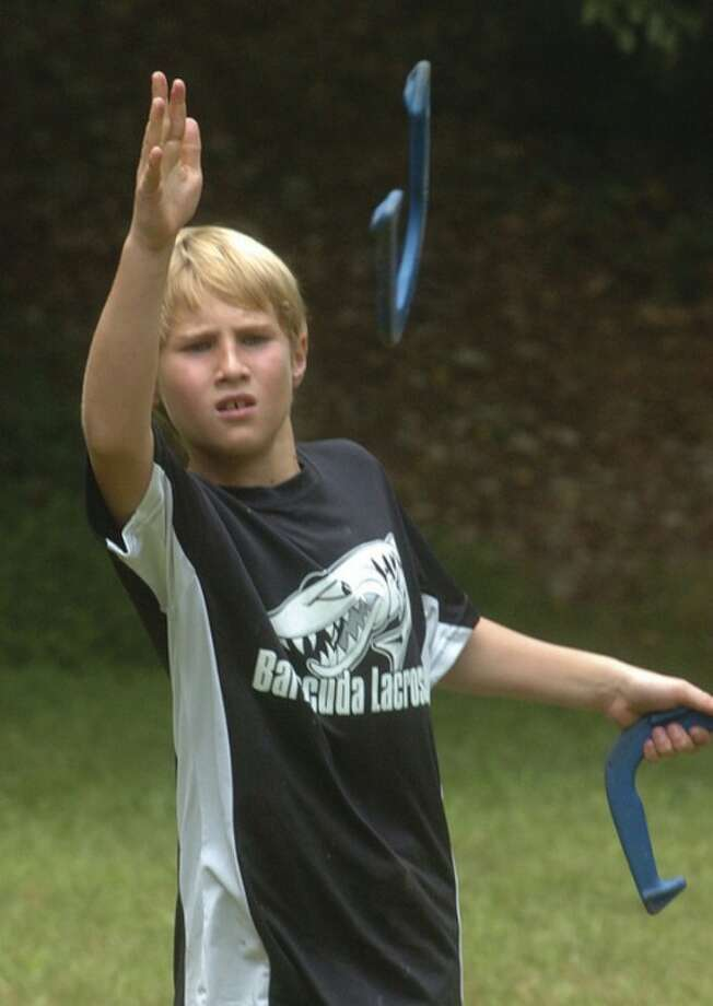 Hour Photo/Alex von Kleydorff. 11yr old Ryan Eckert tries for a ringer in horseshoes at Camp Mahackeno.