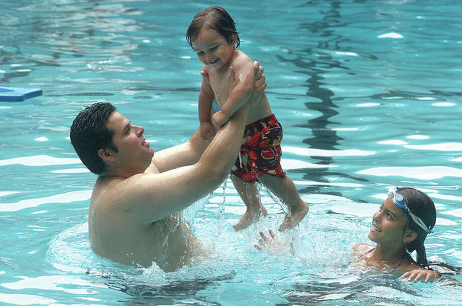 Hour Photo/Alex von Kleydorff Juan Rodas cools off with one-year-old son Johnnie and friend Kianna Gallagher. / 2011 The Hour Newspapers