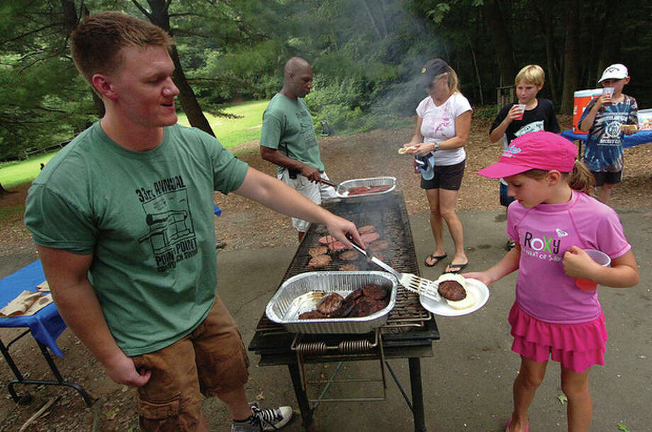 Hour Photo/Alex von Kleydorff Sam Joy serves up some hamburgers to 7-year-old Campbell Eckert at Camp Mahackeno on Sunday. / 2011 The Hour Newspapers