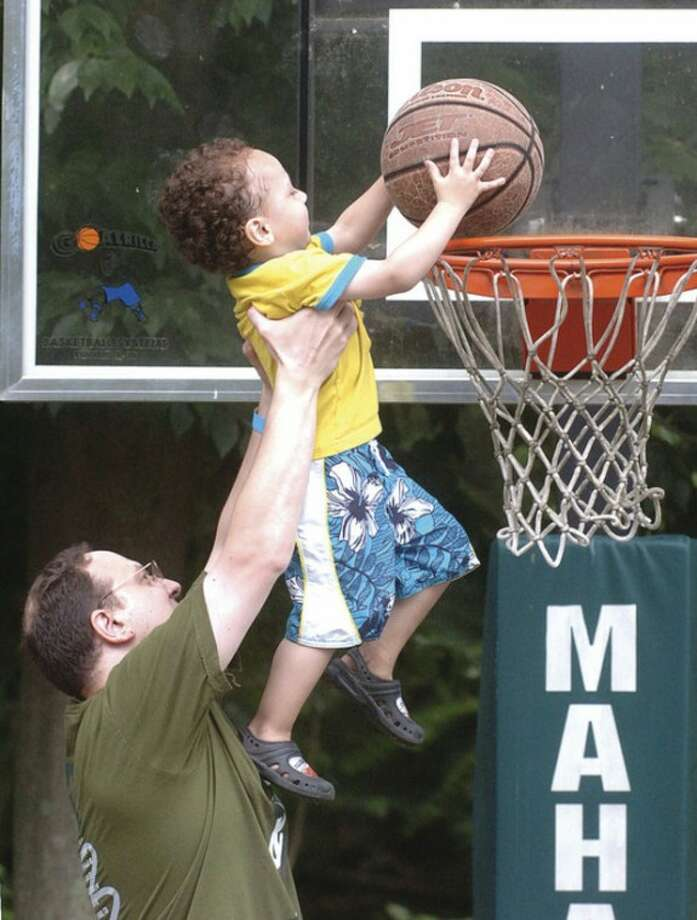 Hour Photo/Alex von Kleydorff Nelson Martinez helps his three-year-old son Benji to the hoop at Camp Mahackeno.