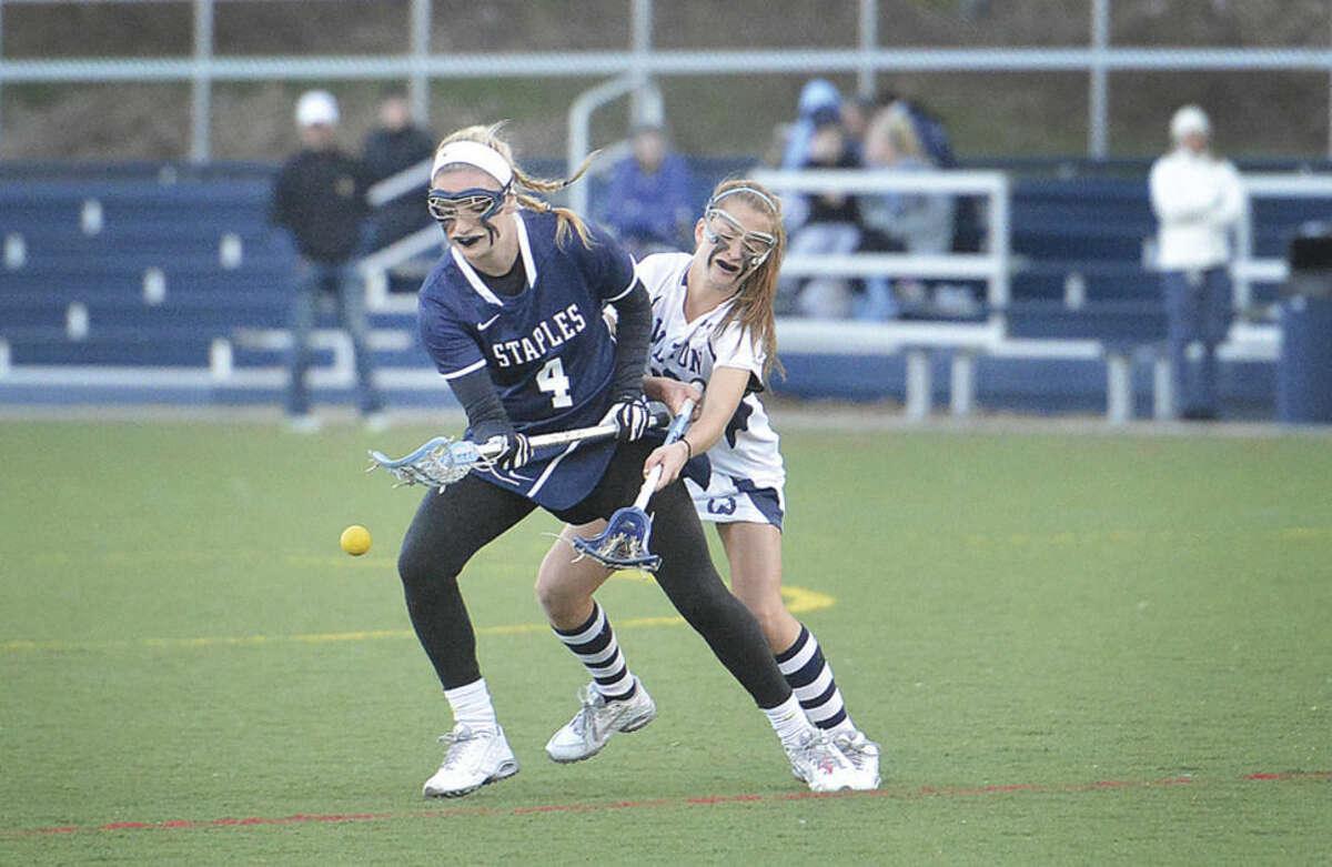Hour photo/Alex von Kleydorff Wilton's Maddie Duffy, rear, knocks the ball from Staples' Jenna McNicholas during Thursday's game in Wilton.
