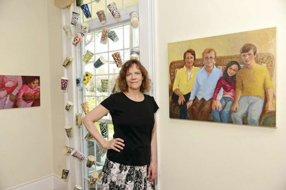 Hour photo / Erik TrautmannArtist Gwyneth Leech with a portrait from her Perfect Families series, is exhibiting her work at the Gallery on the Green at St. Paul's Church.