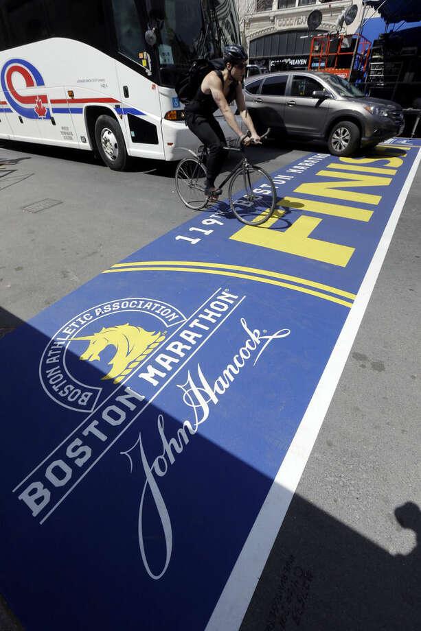 Traffic crosses the newly prepared Boston Marathon finish line Thursday, April 16, 2015, on Boylston Street in Boston. The 119th Boston Marathon will be run on Monday. (AP Photo/Steven Senne)