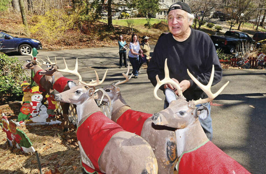 Hour photo / Erik Trautmann At top, Gerri Grasso picks out Christmas decorations at the home of Rick and Joan Setti Saturday, whose elaborate Midwood Road Christmas display has delighted Norwalkers for 26 years, during a tag sale of more than 400 hand-carved figures and thousands of lights. Above, Rick Setti organizes some of the goods.