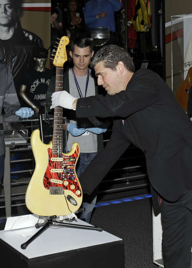 """Greg Harris, president and CEO of the Rock and Roll Hall of Fame and Museum, places a 1961 Fender stratocastor guitar played by Stevie Ray Vaughn at the opening of the Class of 2015 exhibit Friday, April 17, 2015, in Cleveland. Ringo Starr, who was previously enshrined with the Beatles in 1988, will be honored along with pop punks Green Day, soul singer-songwriter Bill Withers, underground icon Lou Reed, guitarist Stevie Ray Vaughan and Double Trouble, Joan Jett and The Blackhearts, The Paul Butterfield Blues Band and The """"5"""" Royales. (AP Photo/Tony Dejak)"""
