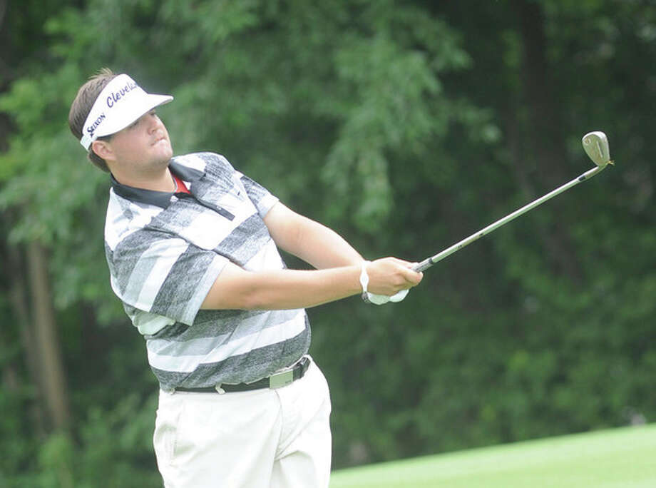 Hour photo/Matthew VinciMike Ballo Jr. of Stamford follows the flight of theball during Monday's first round of the Connecticut Open. Ballo was the leader after shooting a three-under 69 in the opening round.