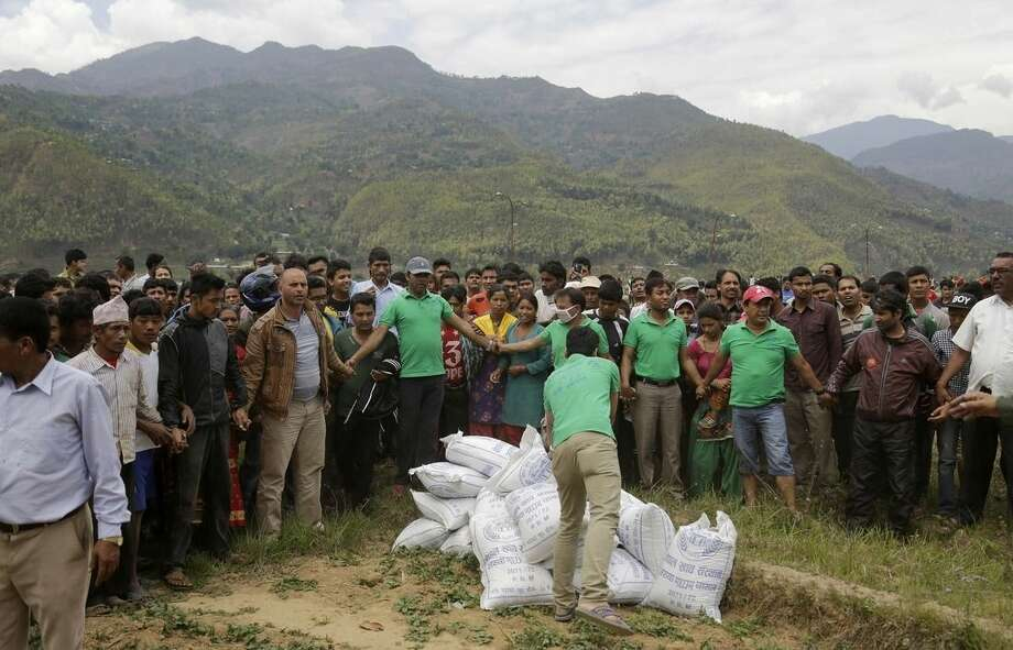 Nepalese volunteers unload relief material brought in an Indian air force helicopter for victims of Saturday's earthquake at Trishuli Bazar in Nepal, Monday, April 27, 2015. The death toll from Nepal's earthquake is expected to rise depended largely on the condition of vulnerable mountain villages that rescue workers were still struggling to reach two days after the disaster. (AP Photo/Altaf Qadri)