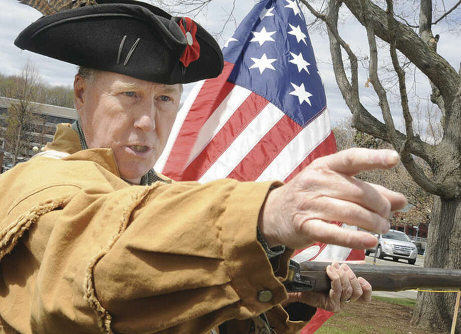 Hour photo/Matthew VinciDavid Perkins, with the Sons of The American Revolution, demonstrates his Brown Bess replica musket at Jesup Green in Westport as the town celebrated Minute Man Day on Sunday.