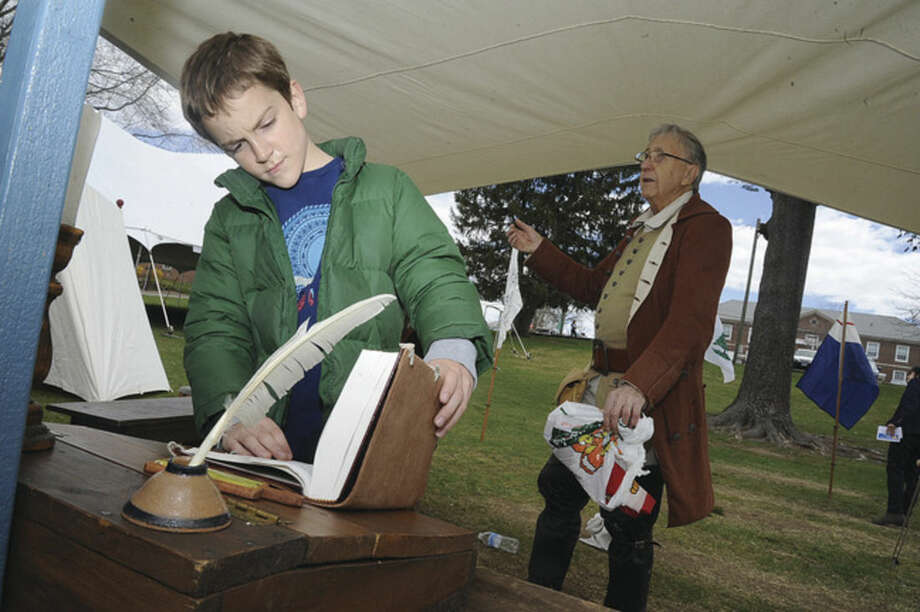 Hour photo/Matthew Vinci10-year-old Julian Fiore looks at artifacts in a Revolutionary encampment set up by the Connecticut Sons of the American Revolution Sunday.