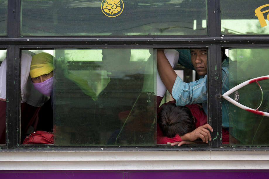 Nepalese people look out from inside a bus where they have taken shelter as it is considered safer in cars than inside houses with repeated aftershocks, in Kalanki neighbourhood of Kathmandu, Nepal, Sunday, April 26, 2015. A powerful aftershock shook Nepal on Sunday, making buildings sway and sending panicked Kathmandu residents running into the streets a day after a massive earthquake devastated the region and destroyed homes and infrastructure. (AP Photo/Bernat Armangue)