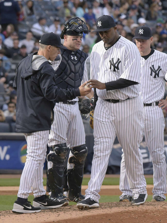 New York Yankees pitcher CC Sabathia, front right, hands the ball to manager Joe Girardi, left, as he leaves an interleague baseball game during the sixth inning against the New York Mets, Saturday, April 25, 2015, at Yankee Stadium in New York. (AP Photo/Bill Kostroun)