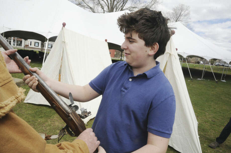 Noah Katz 13, checks out a replica musket era 1775 at Jesup Green in Wstport as the town celebrated Minute Man Day. Hour photo/Matthew Vinci