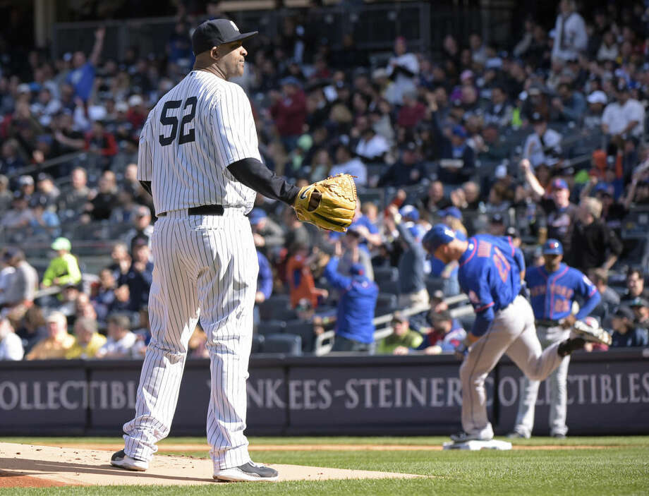 New York Yankees pitcher CC Sabathia, left, waits for a new ball as New York Mets' Lucas Duda rounds the bases with a home run during the first inning of an interleague baseball game Saturday, April 25, 2015, at Yankee Stadium in New York. (AP Photo/Bill Kostroun)